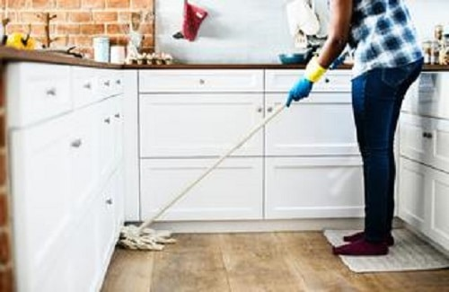 picture of woman cleaning kitchen floor of spiders